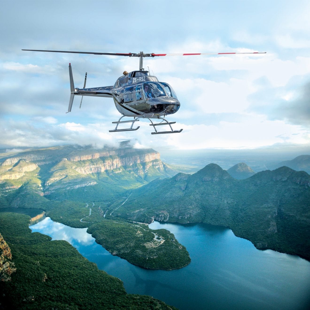 a helicopter flying over African wetlands