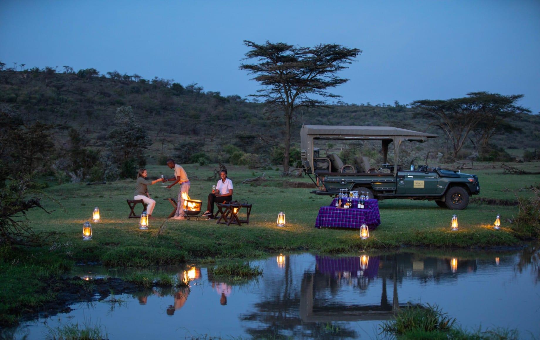 a lake surrounded by candles at Mara Nyika