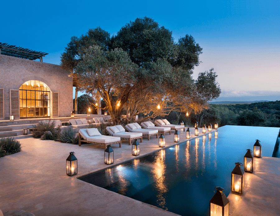 an outdoor patio and pool lit by lanterns at night