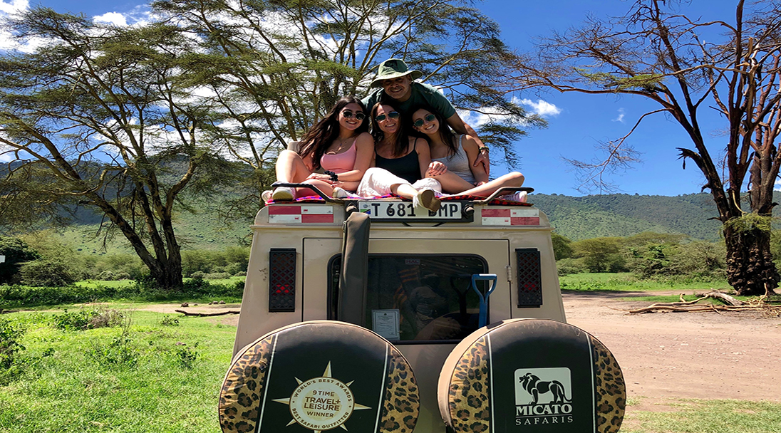 Tourist sitting on top of safari vehicle