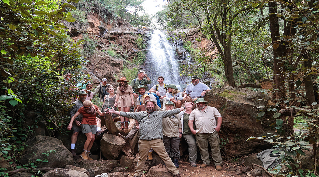 Group of tourist posing in front of a waterfall