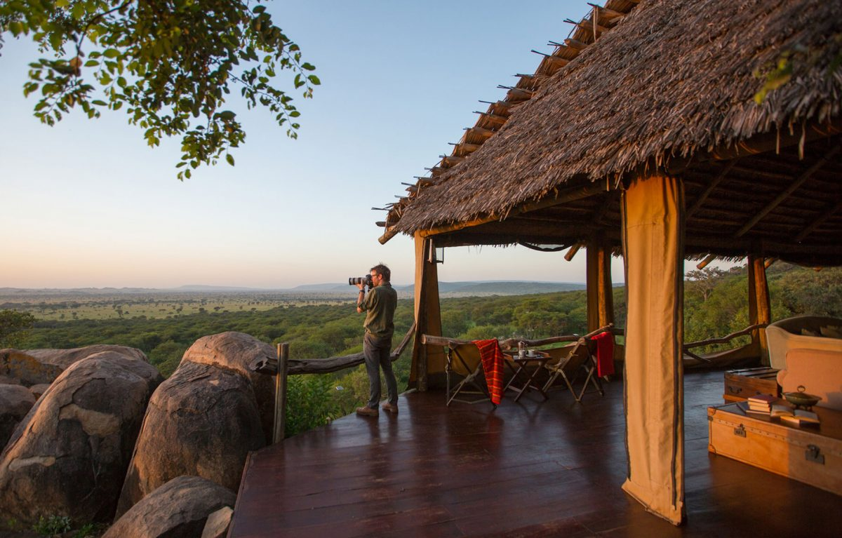 A man taking a picture on the deck of the Serengeti Pioneer Camp.