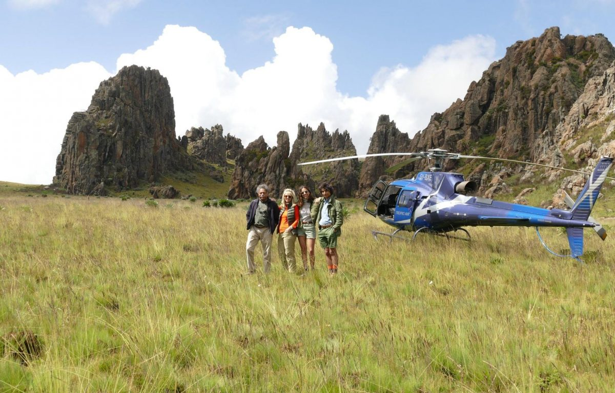 Three people smiling in front of a blue helicopter.