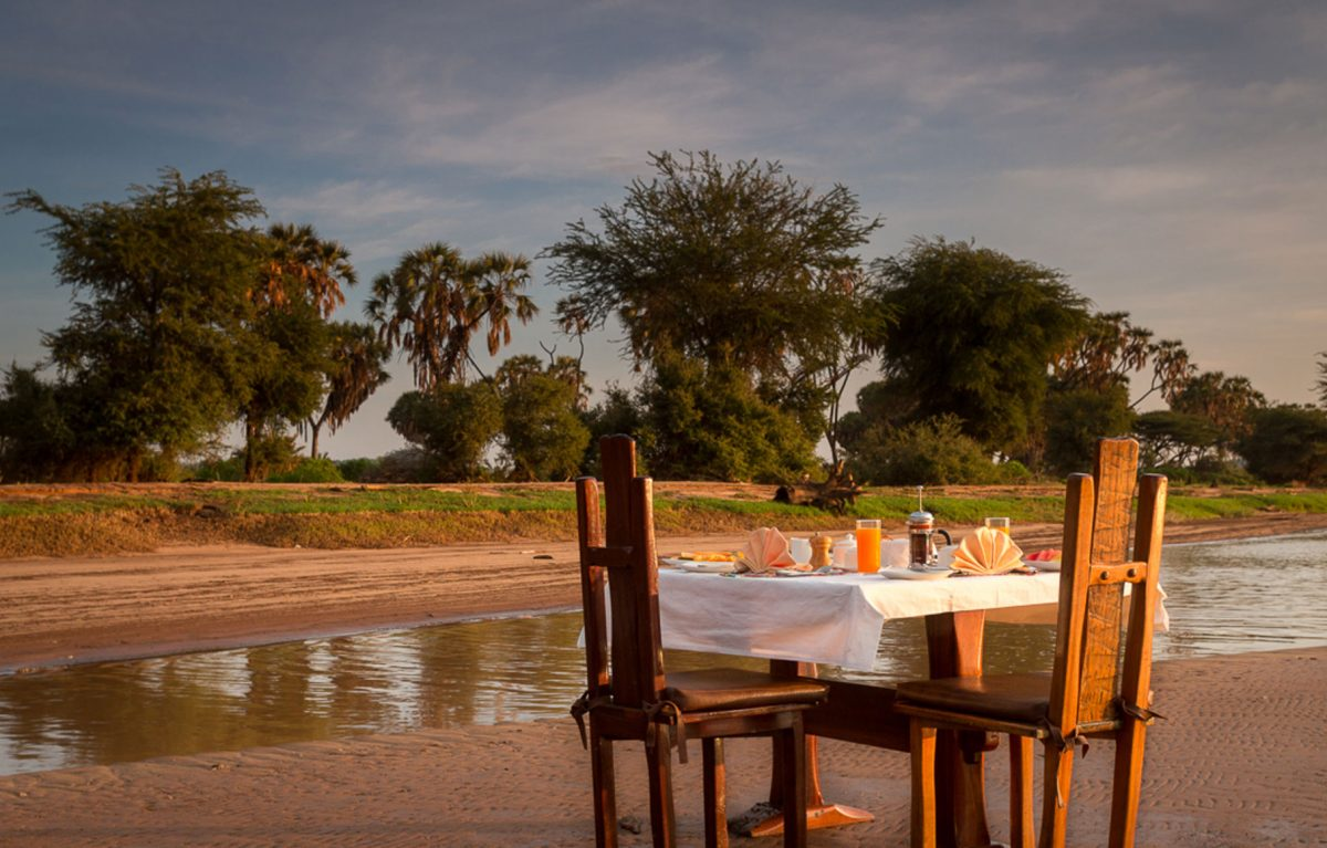 A table set for two by a body of water.
