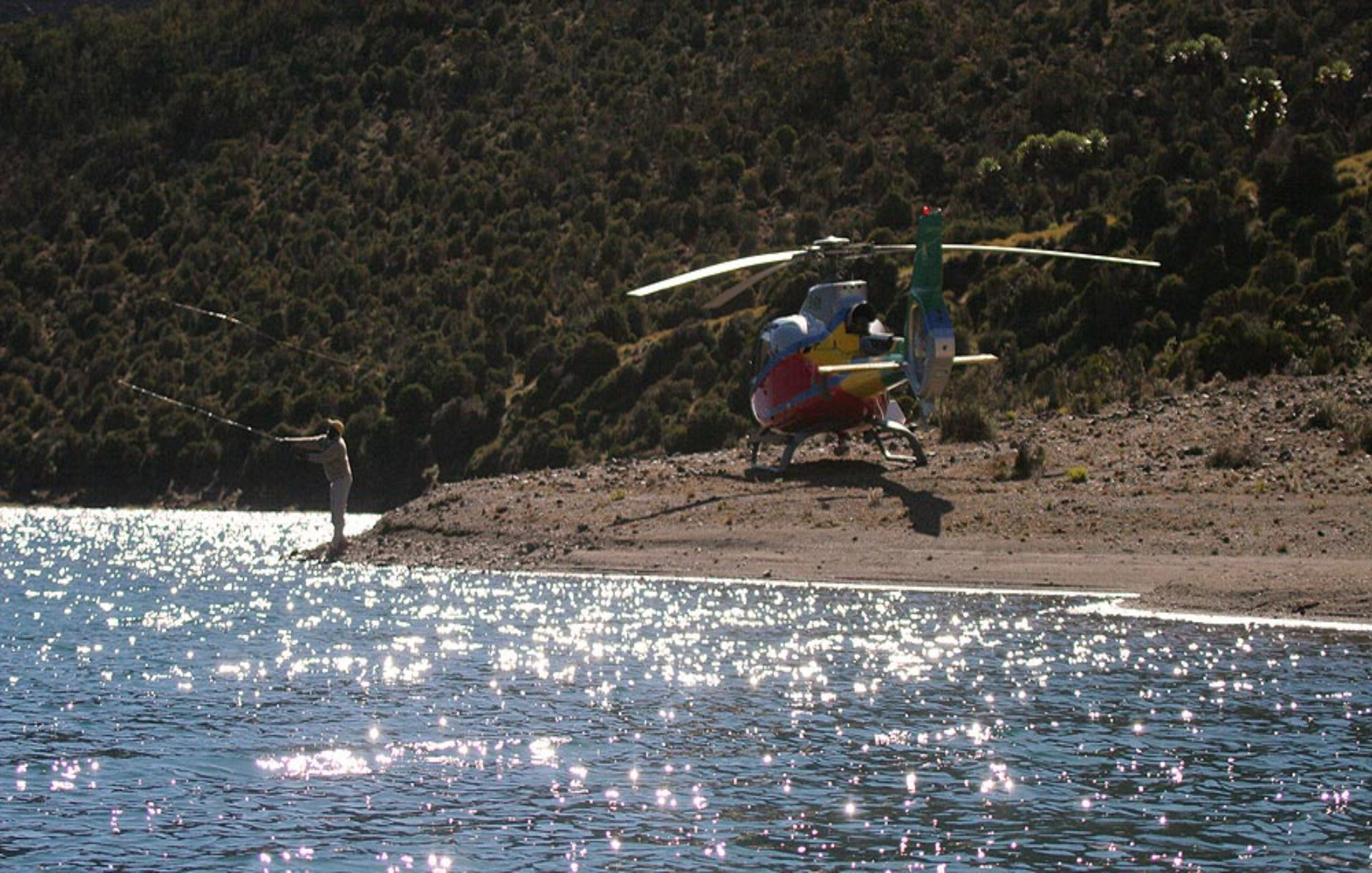 A helicopter over water with a person fishing nearby.