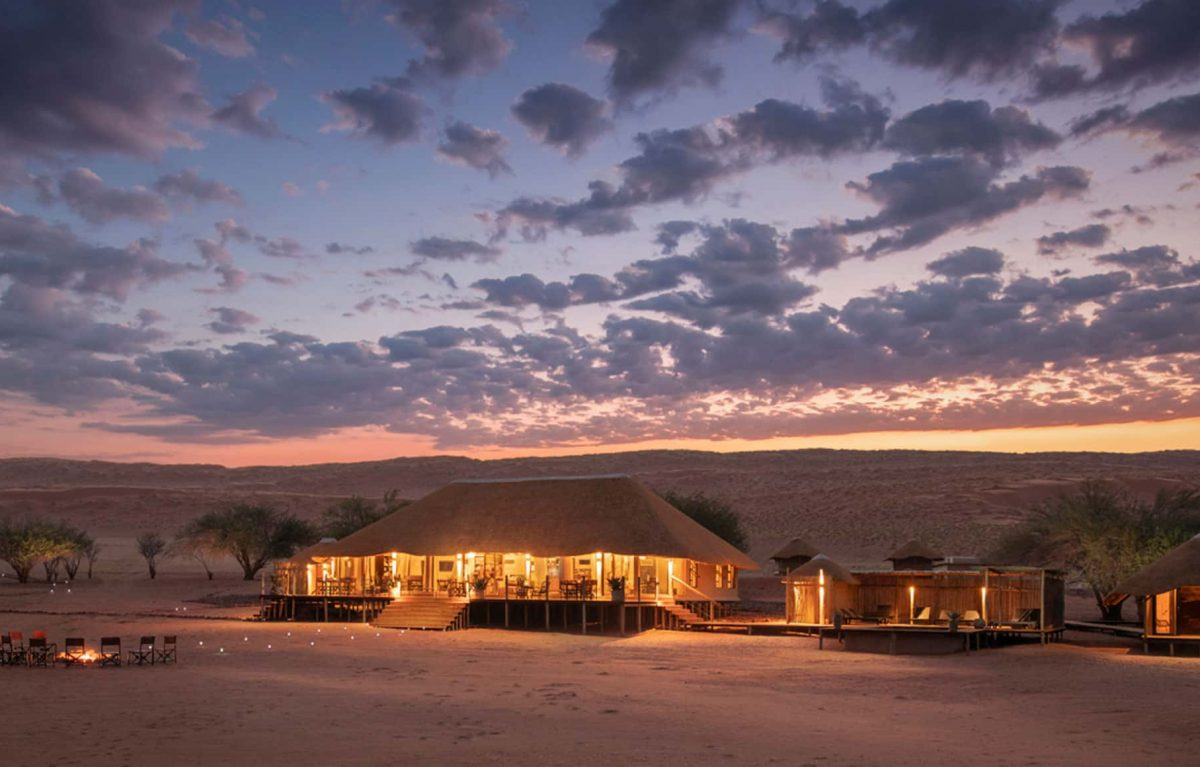 An exterior view of the Kwessi Dunes camp with the sun setting in the background.