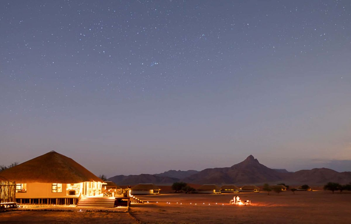 An exterior view of the Kwessi Dunes at night being lit by camp light and the stars in the sky.